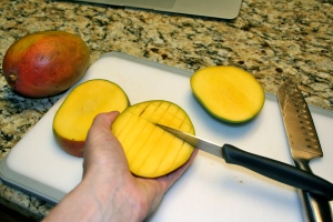 Cut your mango by first slicing off one side and then the other as close to the pit as you can. Then use a knife to cut each side of the mango into squares (not cutting through the skin). Then use a spoon to scoop the mango out.
